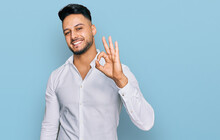 Young Arab Man Wearing Casual Clothes Smiling Positive Doing Ok Sign With Hand And Fingers. Successful Expression.
