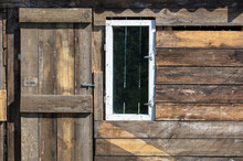 A Door With A Window In A Wooden House.