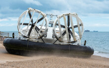 Southsea, England, UK, July 2021. A Passenger Carrying Hovercraft Departing A Concrete Ramp And Crossing A Beach To Enter The Sea. Stern View With Fans To Propel The Craft.