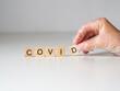 covid - napis z drewnianych kostek, ręka w rękawiczce