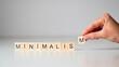 Minimalism - napis z drewnianych kostek na białym tle, dłoń trzymająca kostkę