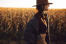Beautiful Stylish Woman In Brown Hat And Vintage Coat Walking In Sunset Light In Autumn Field. Atmospheric Moment. Fashionable Young Hipster Female Walking In Maize Field In Evening Countryside