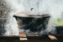 Cauldron Over Bonfire Shrouded In Smoke. Cooking Food Outdoor On Fire In Metal Pot.