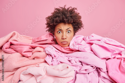Fototapeta Shocked impressed Afro American woman with curly hair surrounded by heap of unfolded clothing isolated over pink background picks clothes for donation busy doing spring cleaning at home