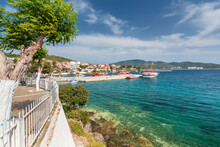 Seascape Featuring A Pier In Front Of A Mediterranean Town With Small Boats For Tourist Trips With Clear Water Near The Coast And Light Clouds On The Blue Sky