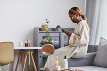 Side View Portrait Of Young African-American Woman Enjoying Skincare Routine At Home And Using Smartphone, Copy Space