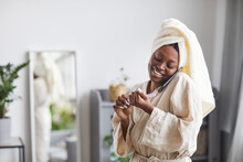 Portrait Of Young African-American Woman Enjoying Beauty Routine At Home And Speaking By Smartphone, Copy Space