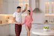Leinwandbild Motiv Happy couple wearing pyjamas and dancing in kitchen