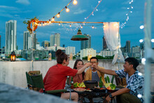Group Of Asian Millennial People Friends Toasting Alcoholic Drink Shot Glasses While Having Outdoor Dinner Party With Eat Barbecue Grill At Rooftop For Meeting Reunion And Holiday Celebration Together