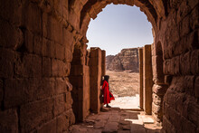 Woman In Red Staring At The Desert In Petra, Jordania