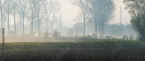 Fotografering Church tower in the morning light whit mist