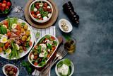 Fototapeta Kawa jest smaczna - Assorted salads on dark gray background. Seasonal food concept.