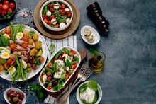 Assorted Salads On Dark Gray Background. Seasonal Food Concept.
