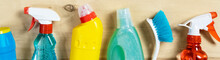 Banner Of Various Cleaning Supplies, Sprays, Bottles And Brush On Wooden Background. House Cleaning Concept
