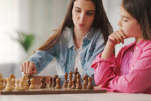Young Mother Teaching Chess To Her Kids