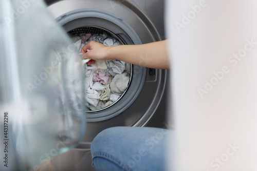 Tela Woman pulling out clean clothes from washing machine in bathroom closeup