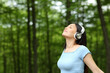 Leinwandbild Motiv Asian woman listening to music breathing fresh air in a forest