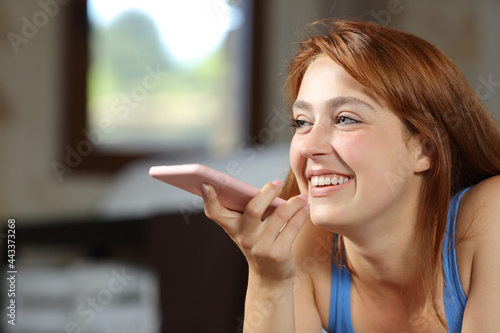 Fotografie, Obraz Happy woman using voice recognition on phone in a bedroom