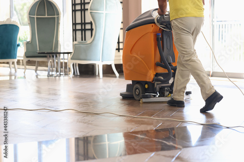 Billede på lærred Cleaner washing floor of hotel lobby with machine closeup