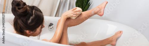 Fotografie, Obraz young woman with hair bun taking bath with loofah in bathtub, banner