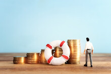 Concept Image Of Stacked Coins And Life Bouy Over Wooden Background. Banking, Funds And Assistance Idea