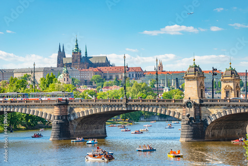 Panoramic view over magnificent Vltava river with Saint Vitus Cathedral near Charles Bridge and walking embarkment in historical downtown of Prague, Czech Republic.