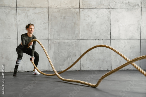 Billede på lærred Young sportswoman with prosthesis working out with battle ropes