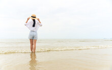 Outdoor Summer Portrait Of Young Asian Woman In Straw Hat Looking To The Sea At Tropical Beach, Enjoy Freedom Time, Fresh Air And Leisure Travel Vacation.