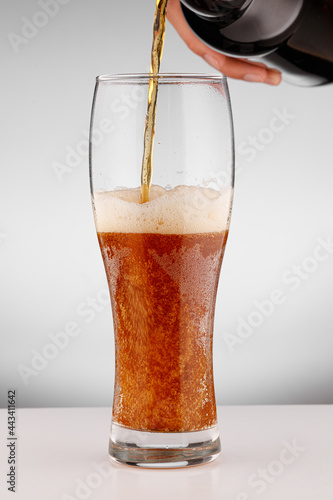 Photo Glass with light brown beer on a white background
