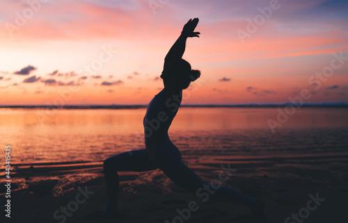 Slika na platnu Unrecognizable slim woman performing yoga pose on embankment during sunset