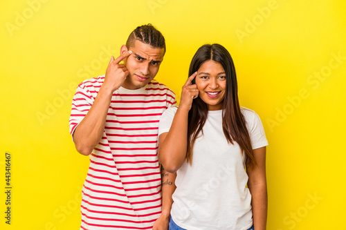 Tablou Canvas Young latin couple isolated on yellow background showing a disappointment gesture with forefinger