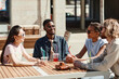 Diverse group of young people enjoying cocktails while sitting at cafe table outdoors lit by sunlight