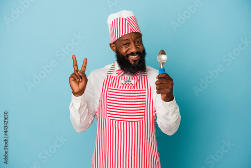Tela African american ice cream maker man holding an ice cream scoop isolated on blue background showing number two with fingers