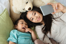 High Angle View Of Mother And Asian Kid Taking Selfie On Smartphone Near Teddy Bear On Bed