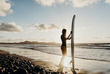 Woman With Surfboard Standing Near Waving Sea At Sunset