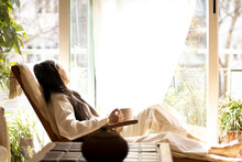 Mature Woman Sitting On A Sofa Looking The Terrace.