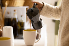 Hand Of A Woman Pouring Coffee With An Italian Coffee Maker In A Kitchen