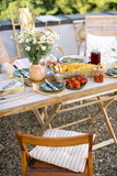 Beautifully served wooden table in natural boho style outdoors. Dining table decorated with field flowers, dishes and fresh food