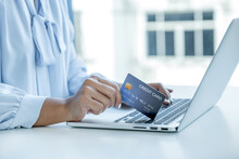 Consumer Woman Hand Holding A Mock Up Credit Card, Ready To Spending Pay Online Finance Shopping According To Discount Products Via Laptop From Home Office