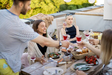 Sad And Thoughtful Woman Sitting Separately On A Party With Friends Outdoors, Young People Dining On A Rooftop Terrace