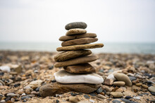 Tiny Stone Cairn On Rocky Beach Shore