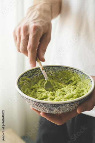 Photo Male chef mashing avocado with fork in a bowl