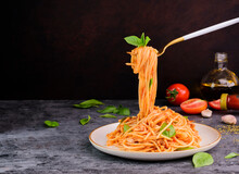The Fork Is Scooping Up The Classic Italian Spaghetti Pasta With A Mouthwatering Tomato And Basil Sauce. Freshly Cooked Food Is Placed On A Plate Set On A Wooden Table. On A Dark Background