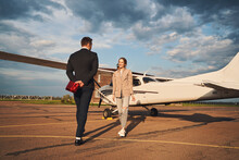 Beautiful Couple In Love Standing Near Plane At Airfield