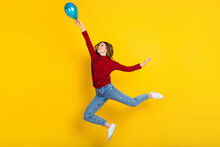Full Body Profile Photo Of Cool Millennial Lady Jump With Balloon Wear Sweater Jeans Isolated On Vivid Yellow Color Background
