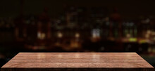Empty Wooden Table Top With Lights Bokeh On Blur Cityscape Background.