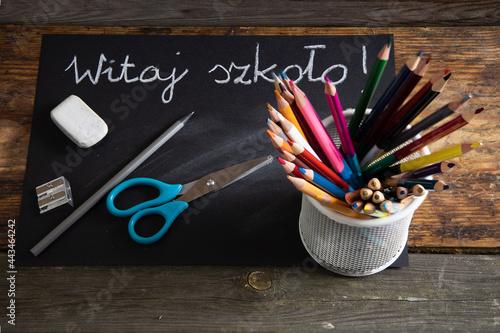 Powrót do szkoły. Nożyczki ołówek gumka i kolorowe kredki na tle tablicy.