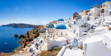 Panorama Of The Whitewashed Houses And Blue Domed Churches Of The Village Oia, Santorini Island, Greece, During Summer Time