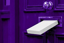 Postal White Box Mailbox Letterbox The Parcel Is Delivered Through The Parcel Door Opening Background.Photo Of Gift Idea Post Box Package And Old Aged Grunge Vintage Retro Violet Purple Door Wall.