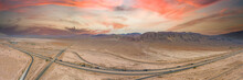 A Stunning Aerial Panoramic Shot Of Majestic Mountain Ranges In A Vast Desert Land With Powerful Clouds With Freeways Filled With Cars In Yerma California